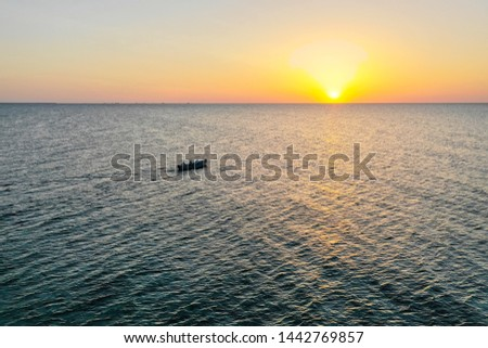 A boat sailing on the sea, early in the morning, beautiful sunrise as background. Aerial view Seascape. Local people fishing on a wooden long tail boat. Silhouette fisherman wooden boat during sunrise #1442769857