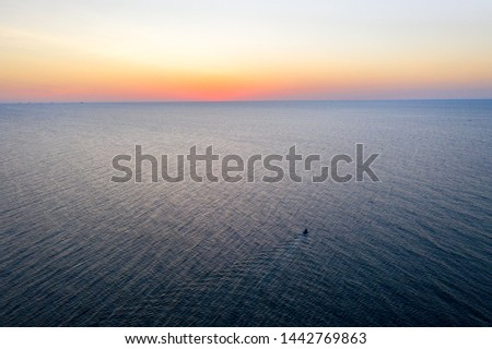 A boat sailing on the sea, early in the morning, beautiful sunrise as background. Aerial view Seascape. Local people fishing on a wooden long tail boat. Silhouette fisherman wooden boat during sunrise #1442769863