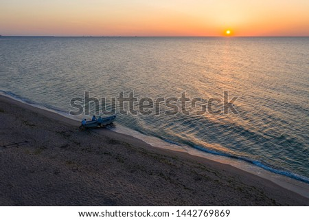 A boat sailing on the sea, early in the morning, beautiful sunrise as background. Aerial view Seascape. Local people fishing on a wooden long tail boat. Silhouette fisherman wooden boat during sunrise #1442769869
