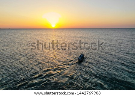 A boat sailing on the sea, early in the morning, beautiful sunrise as background. Aerial view Seascape. Local people fishing on a wooden long tail boat. Silhouette fisherman wooden boat during sunrise #1442769908