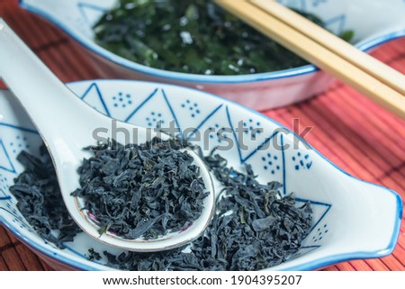 A boat-shaped ceramic bowl containing dried wakame seaweed and a ceramic spoon, in the background an equal bowl with regenerated seaweed in water