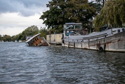 A Boat sunk at its moorings on the River Thames in England.