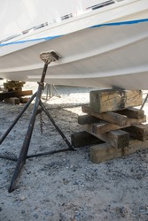 A boat, supported by stacked wooden cribbage and a metal stand, in a boatyard is having regular maintenance and a coat of bottom paint applied to it.