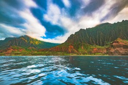 A boat tour view of Kalalau beach and Kalalau Valley during the sunset hour in the colorful and dramatic Nā Pali Coast State Wilderness Park on the island of Kauai, Hawaii, United States.