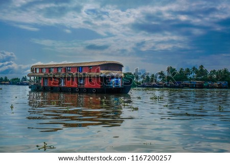 A boathouse in backwaters of Alleppey in Kerala, India with blue sky and clouds with reflection in water #1167200257