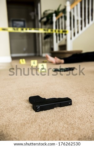 a body on the ground of a crime scene with a gun in the foreground.