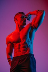 A bodybuilder with a beard is posing with a flexed bicep under the blue and red light. An athletic guy is demonstrating his sporty torso. An athlete in shorts after a workout.