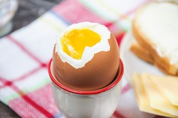 A boiled egg and a sandwich with butter and cheese