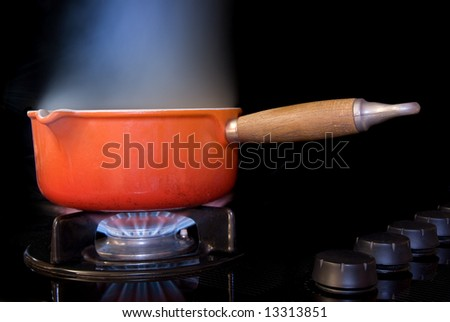 A boiling pot of water on a black stove. The steam in this image is real and not a PS overlay.  I used a very slow shutter speed and backlighting to catch the steam rising as the water boiled.