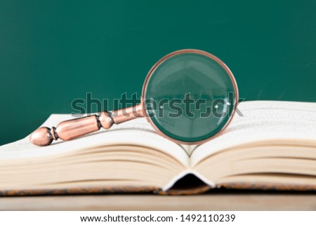 A book and book on a blackboard with a magnifying glass #1492110239
