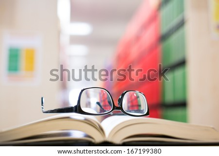 a book lying on the bookshelf with a glasses in Library