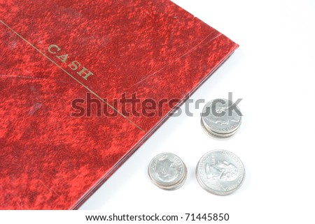 A booklet that says cash on it for keeping track of finances and coins next to it.