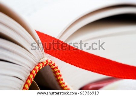 A bookmark in a book helps to find the correct page. Macro with extremely shallow depth of field