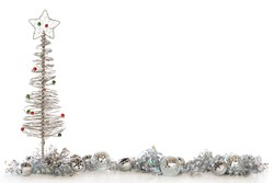 A border composed of a wire Christmas tree, bells, shimmery bulbs and curly ribbon, all in sliver.   Isolated on white with plenty of room for your text.