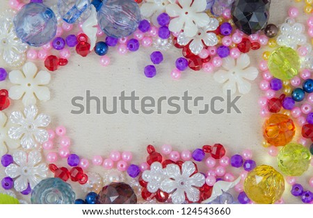 A border made of a red, purple and green mardi gras mask and blue, green,and purple plastic beads