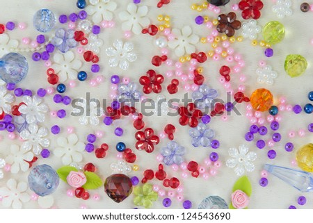 A border made of a red, purple and green mardi gras mask and blue, green,and purple plastic beads - stock photo