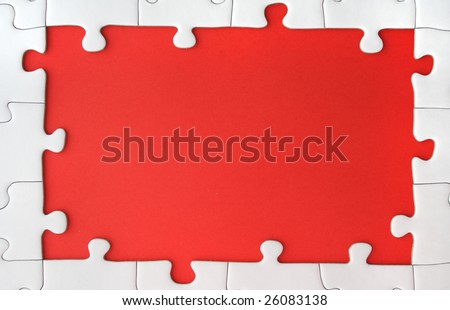 A border of white puzzle pieces around a red ground.