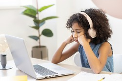 A bored African schoolgirl in headphones sits at the desk at home watching online classes on the laptop without enthusiasm and she is uninteresting. E-learning concept