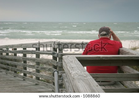 A bored old man, watching the a storm roll in over the ocean.
