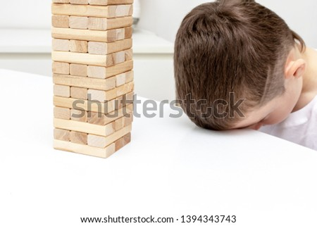 A bored preteen caucasian boy trying to play wooden block tower board game to entertain himself. #1394343743