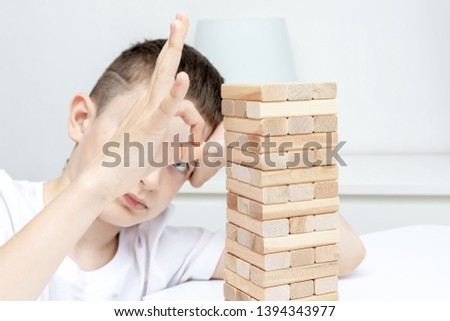 A bored preteen caucasian boy trying to play wooden block tower board game to entertain himself. #1394343977