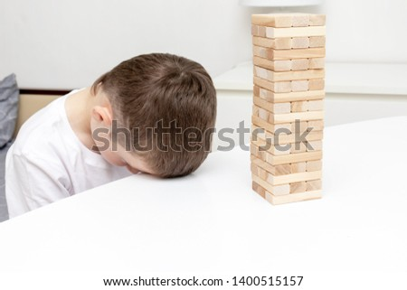 A bored preteen caucasian boy trying to play wooden block tower board game to entertain himself. #1400515157