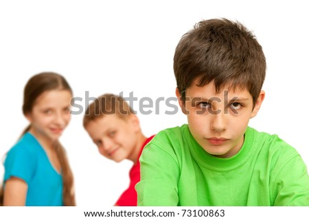 A boring kid is sitting against his happy friends; isolated on the white background