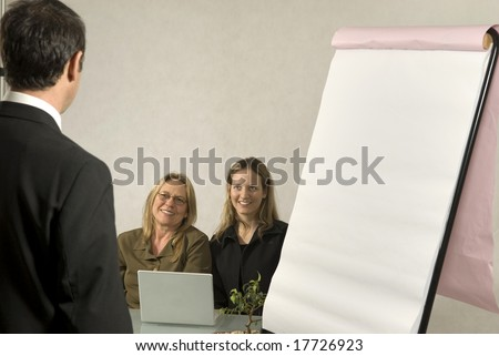 A Boss in instructing his employees in a business meeting.  The two girls are smiling at him.  Horizontally framed shot.