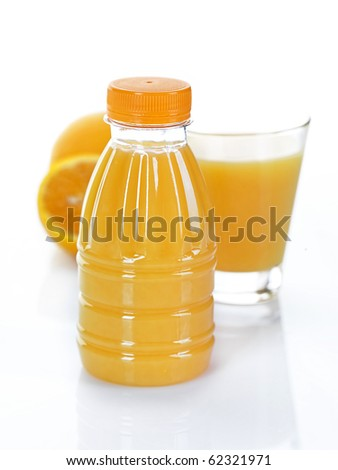 a bottle and a glass of fresh orange juice decorated by a whole and a halved orange