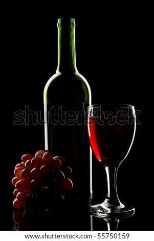A bottle and glass of red wine with grapes