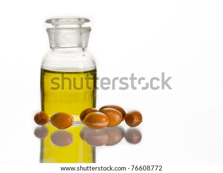 A bottle of argan oil and some argan fruits on white. Argan oil is used for cosmetic products