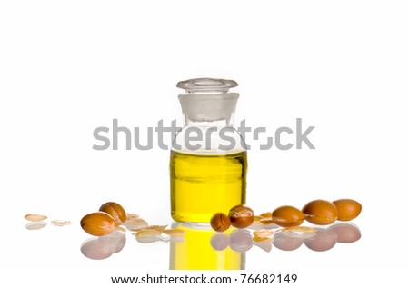 A bottle of argan oil on white background with argan fruits.
