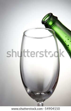 A bottle of beer about to get poured into a wine glass.