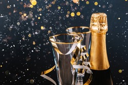A bottle of champagne and glasses on a festive background with lights and snow. Place for text