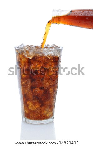 A Bottle of cola soda pouring into a glass filled with ice cubes over a white background with reflection.
