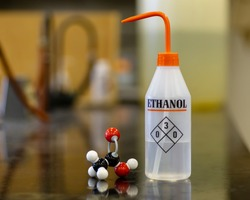 A bottle of ethanol with its chemical structure on a laboratory bench.