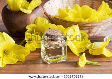 A bottle of evening primrose oil with fresh evening primrose flowers in the background #1029509956