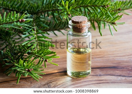 A bottle of fir essential oil with young fir branches on a wooden table