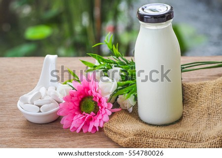 A Bottle of fresh Milk and Selective Focus A Calcium white tablet a good supplement pills for woman bone in Healthy care Concept: decorated with pink and white flower