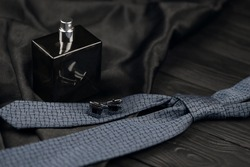A bottle of mens cologne and cufflinks with blue tie lie on a black luxury fabric background on a wooden table. Mens classic accessories. Shallow DOF