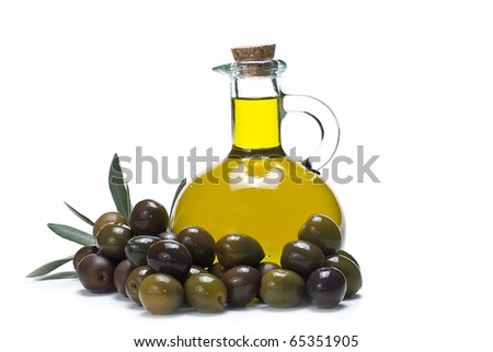 A bottle of olive oil and a lot of olives.