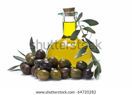 A bottle of olive oil and a lot of olives around it.