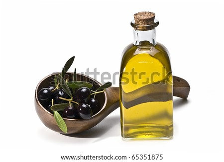 A bottle of olive oil and a spoonful of premium olives isolated on a white background.
