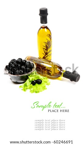 A bottle of olive oil with herbs and black olives isolated on a white background.