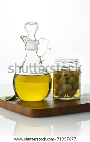 A bottle of olive oil with olives