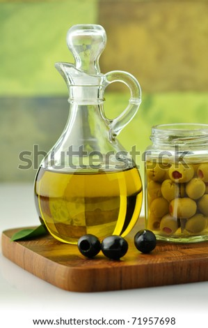 A bottle of olive oil with olives - stock photo