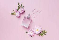 A bottle of perfume, flowers and petals on pink background. Floral fragrance, creative flat lay composition