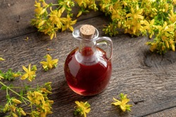 A bottle of red oil made from St. John's wort flowers on a table