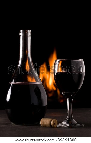 A bottle of red wine and a glass in front of a fireplace