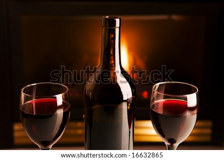 A bottle of red wine and two glasses in front of a fireplace
